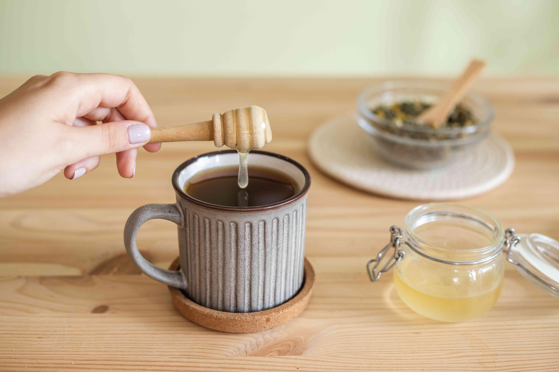 hand uses wooden honey dipper to drip honey into mug of hot tea