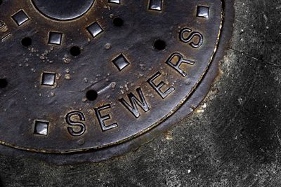 A close up of a sewers man hole cover on pavement.