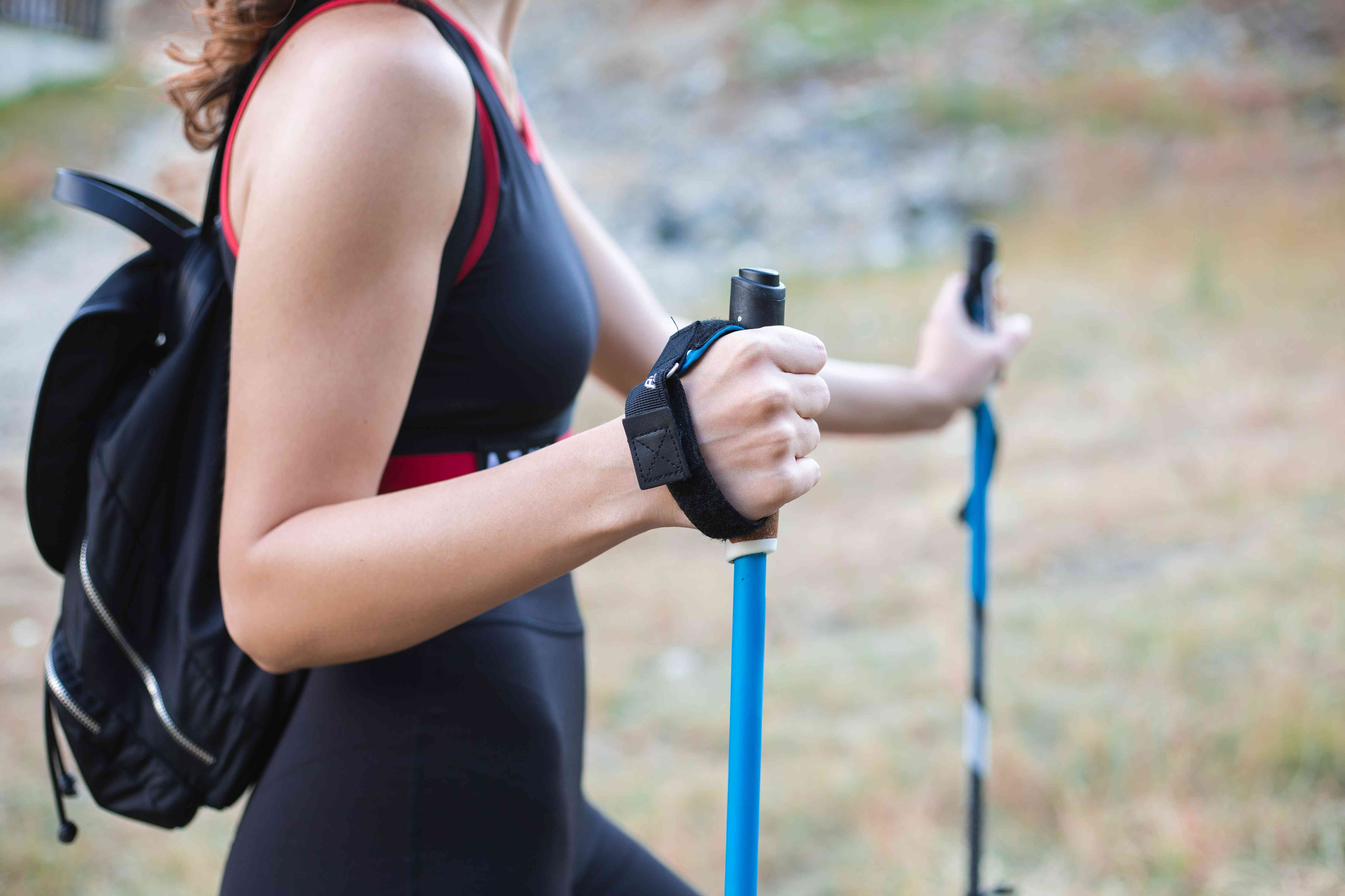 woman in workout clothes and backpack uses blue walking poles on outside walk
