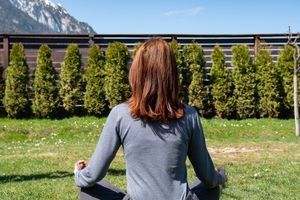 back shot of woman meditation in green lawn with hedges and mountains in background