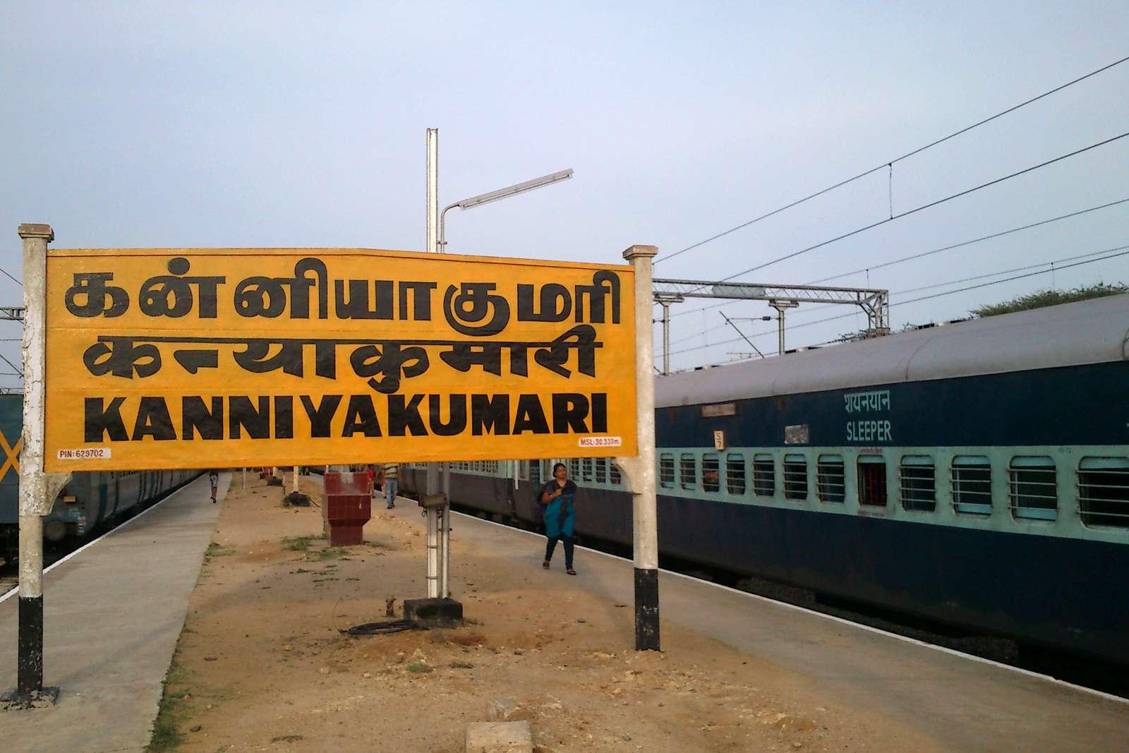 Large orange Kanyakumari railway station sign with sleeper train on tracks