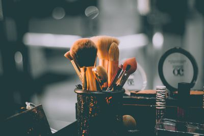 Makeup brushes in a container, surrounded by cosmetics