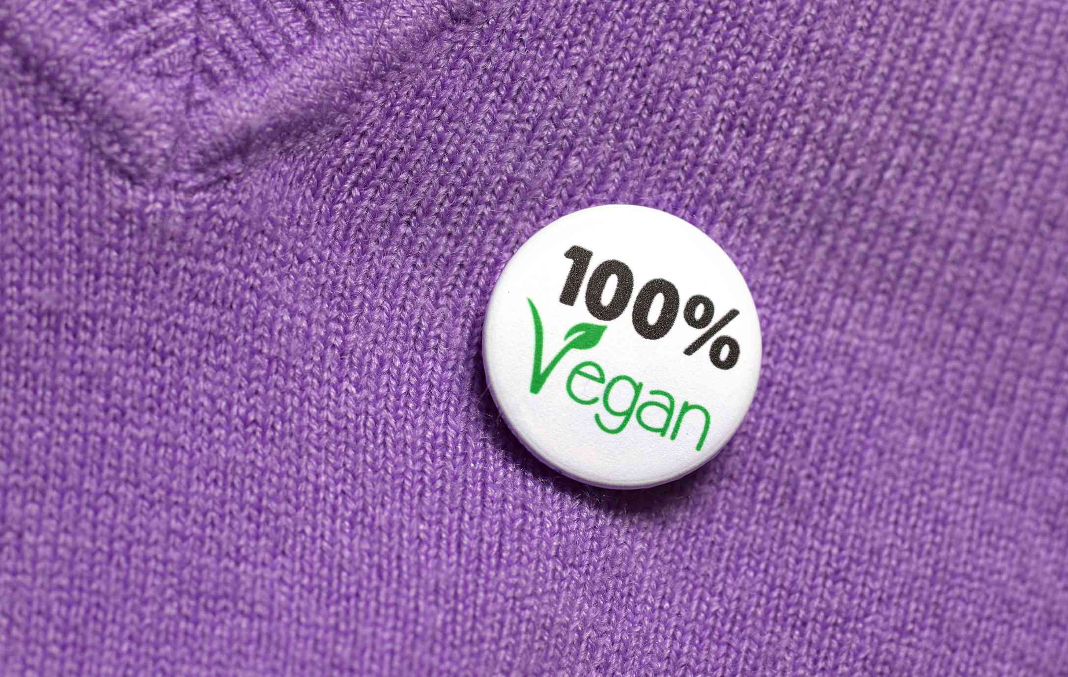 A purple sweater with a button that says 100% vegan.