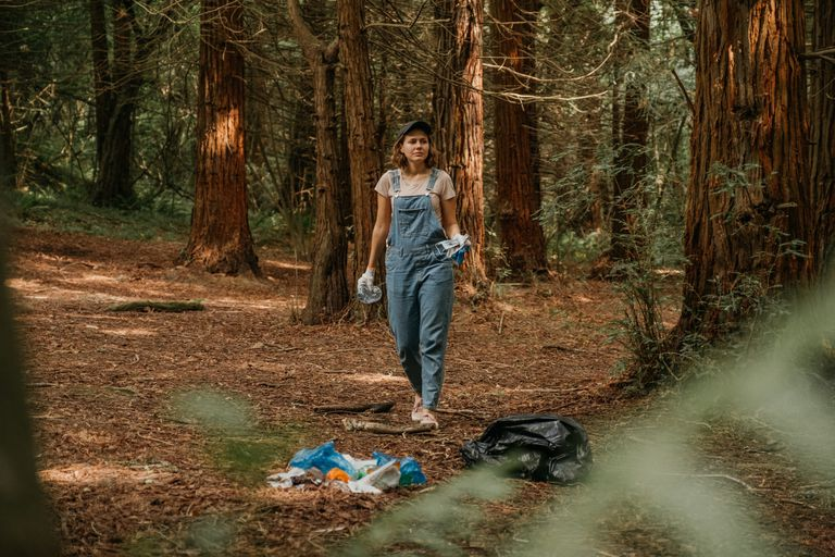 A woman in overalls picks up garbage in the forest.