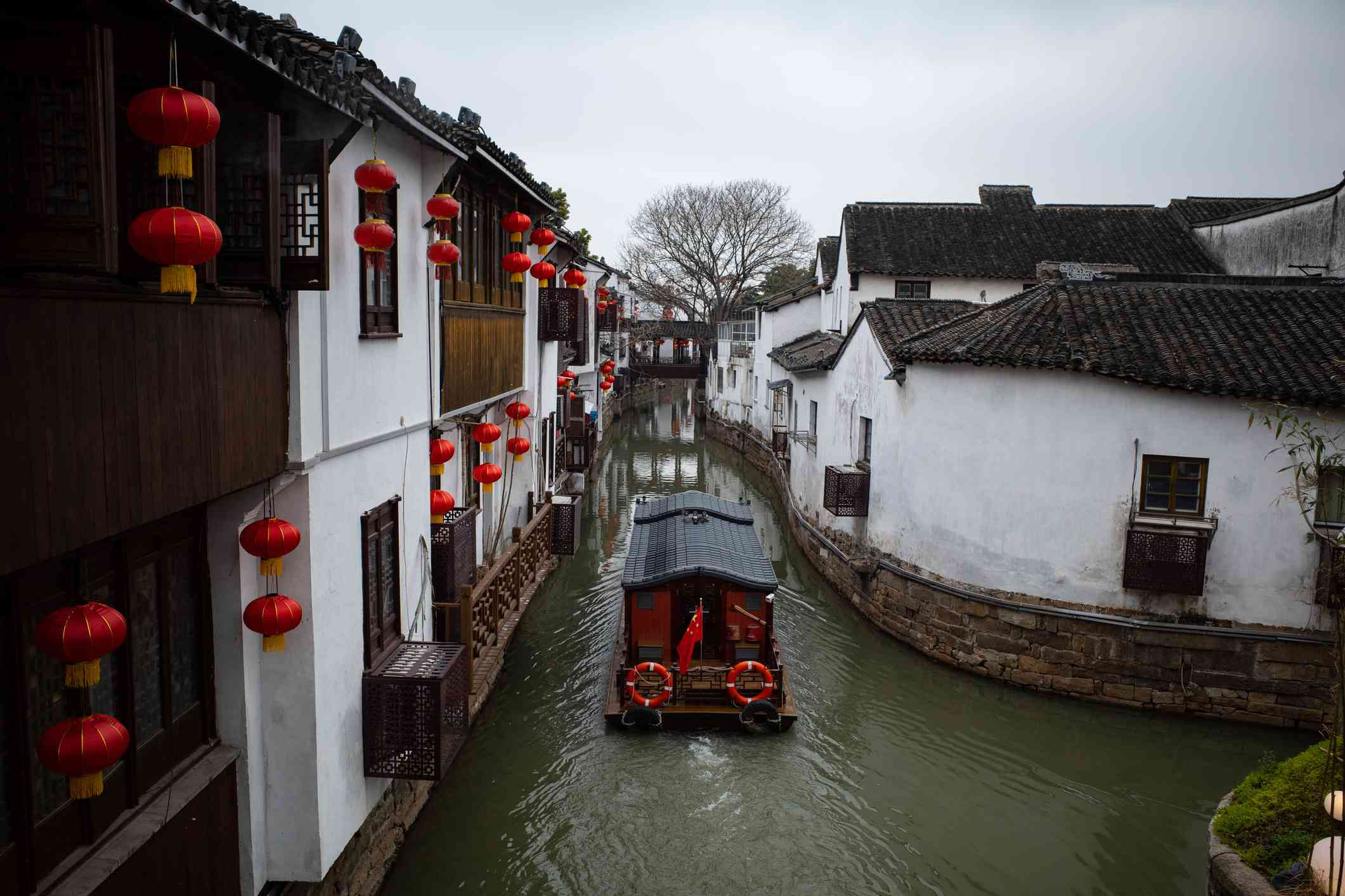black boat with red trim traveling through the water in the old water town of Suzhou