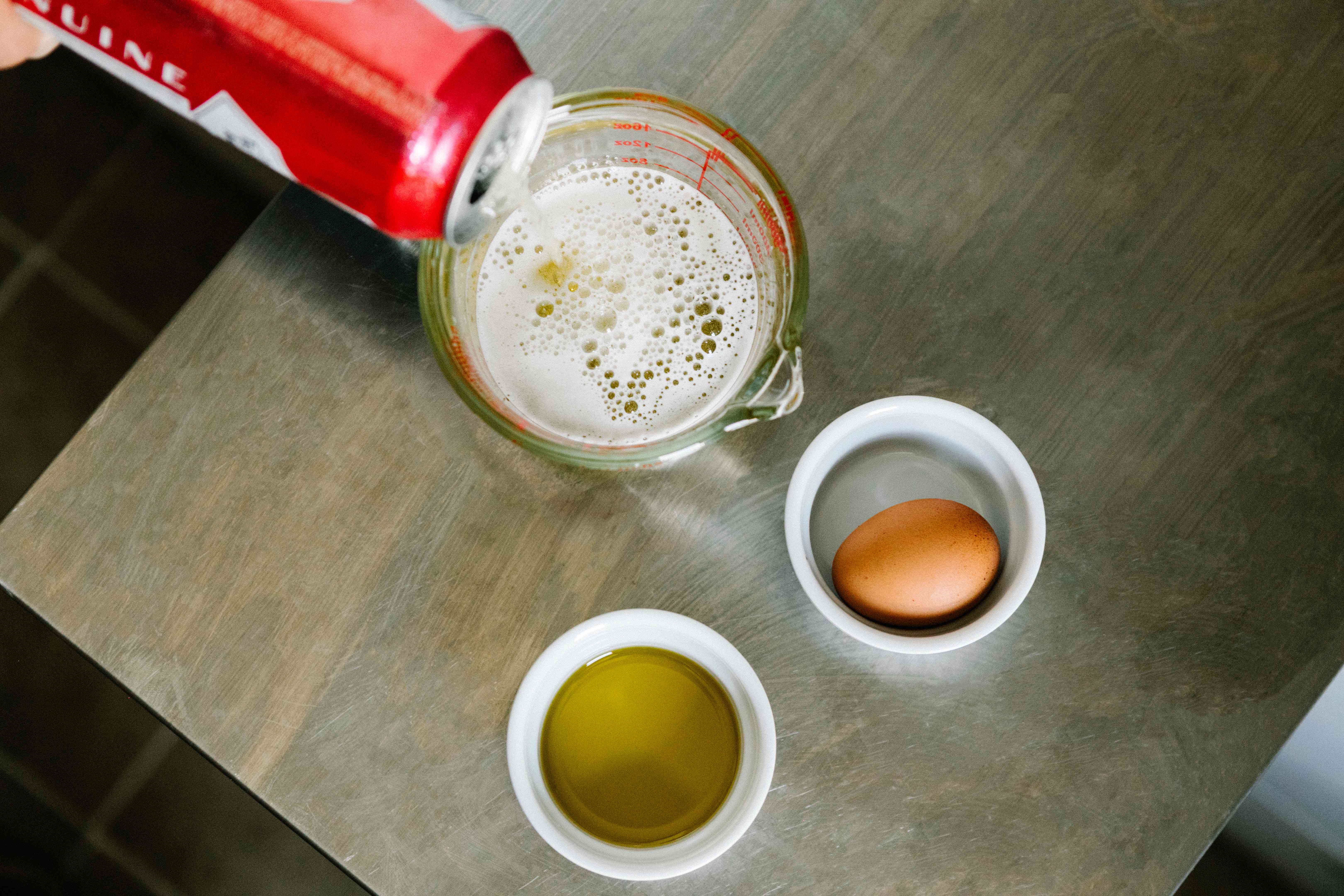 can of beer poured into measuring cup, next to olive oil and egg for hair mask