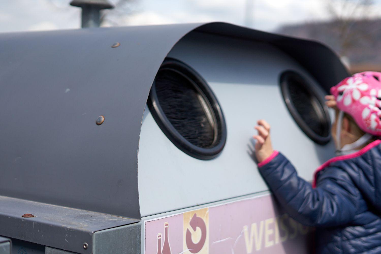 little kid wearing helmet peeks in a recycling drop-off bin
