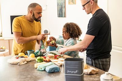 Fathers helping daughter make a sandwich with a reusable produce bag, cloth sandwich wraps, and a small compost bucket on the counter