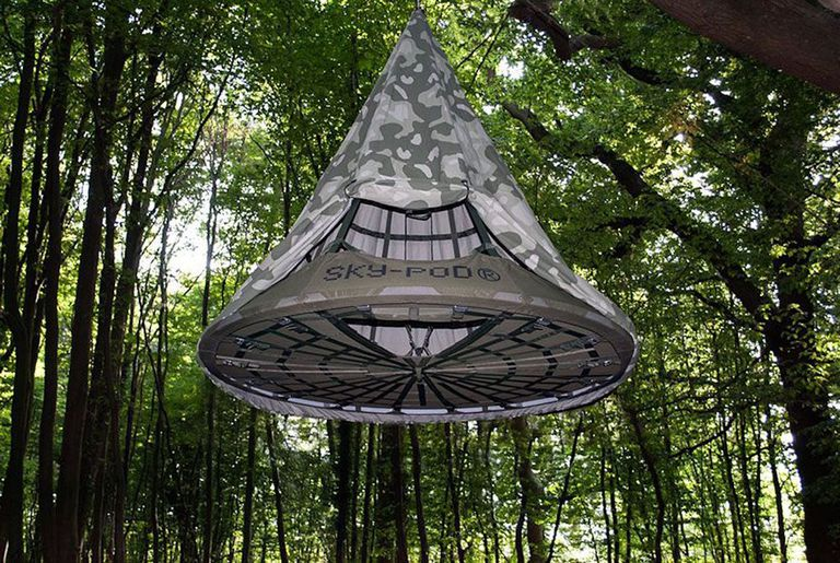 Sky Pod tent hanging from a tree in a forest