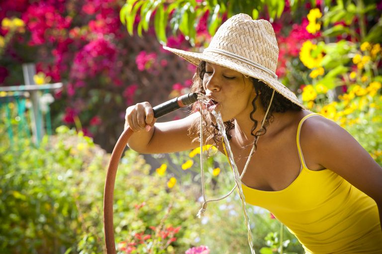 A Black woman with a straw hat drinks water out of a hose in a garden.