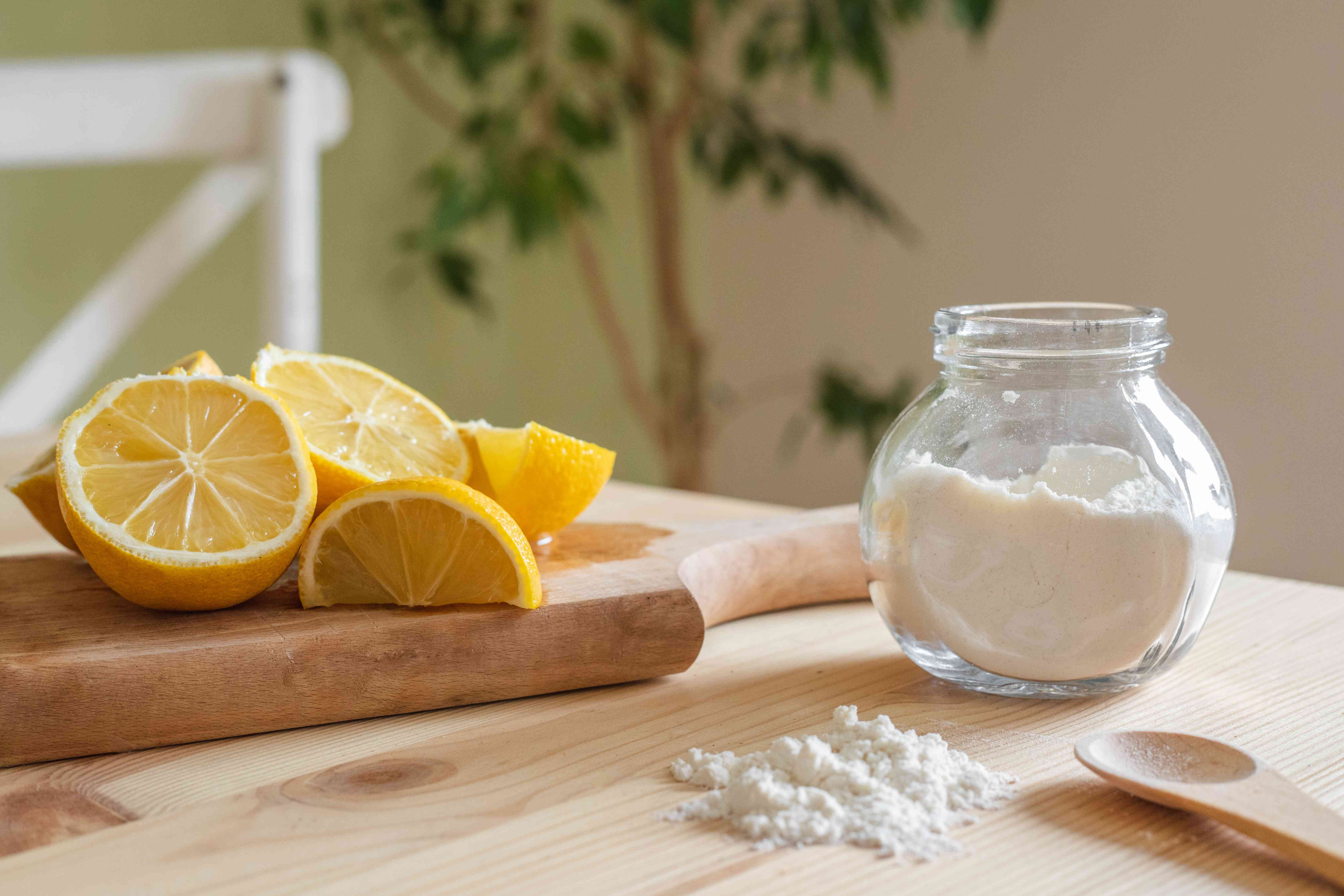 spilled stevia sugar from glass jar on wooden table next to cut lemons