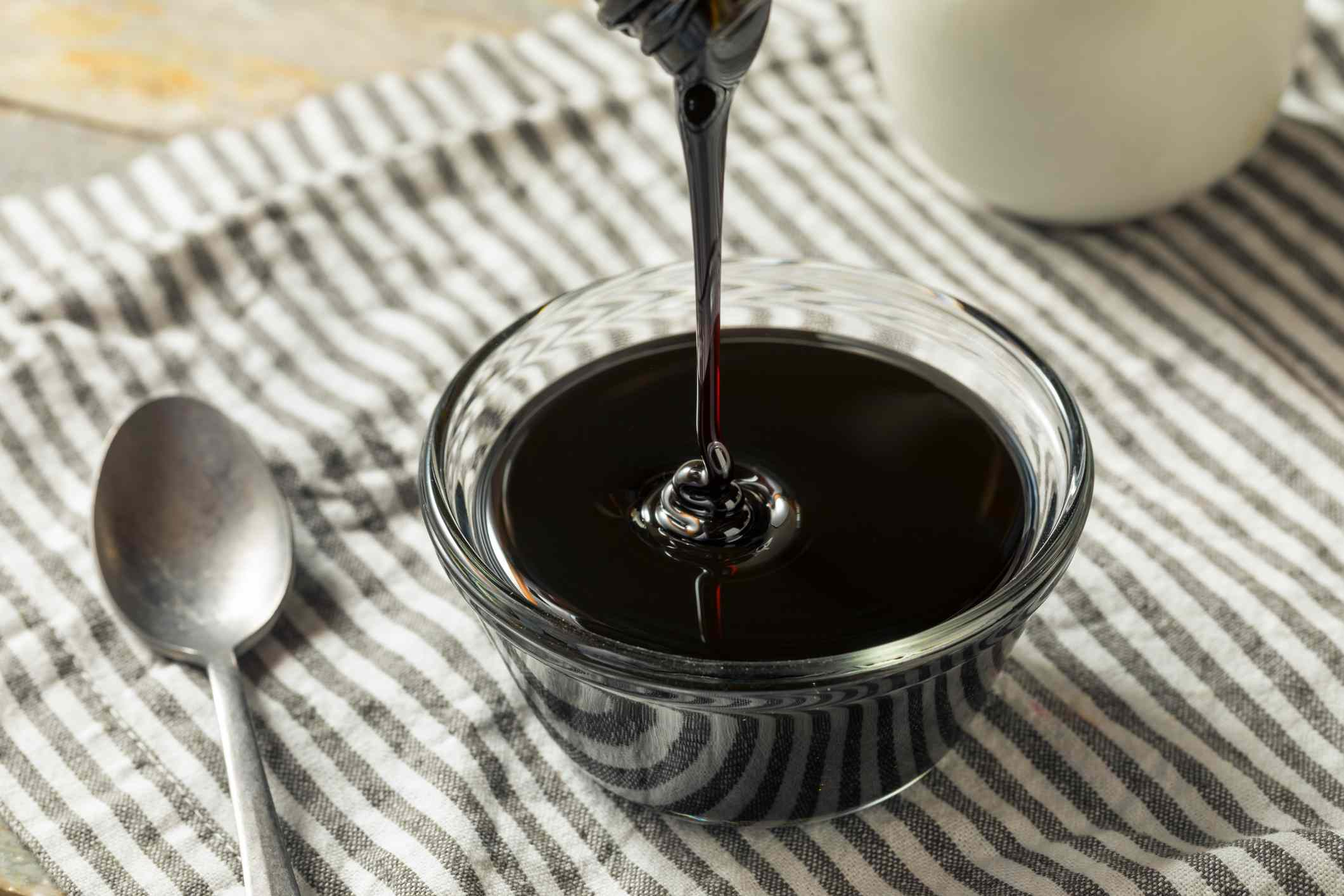 High-angle view of black molasses being poured into bowl