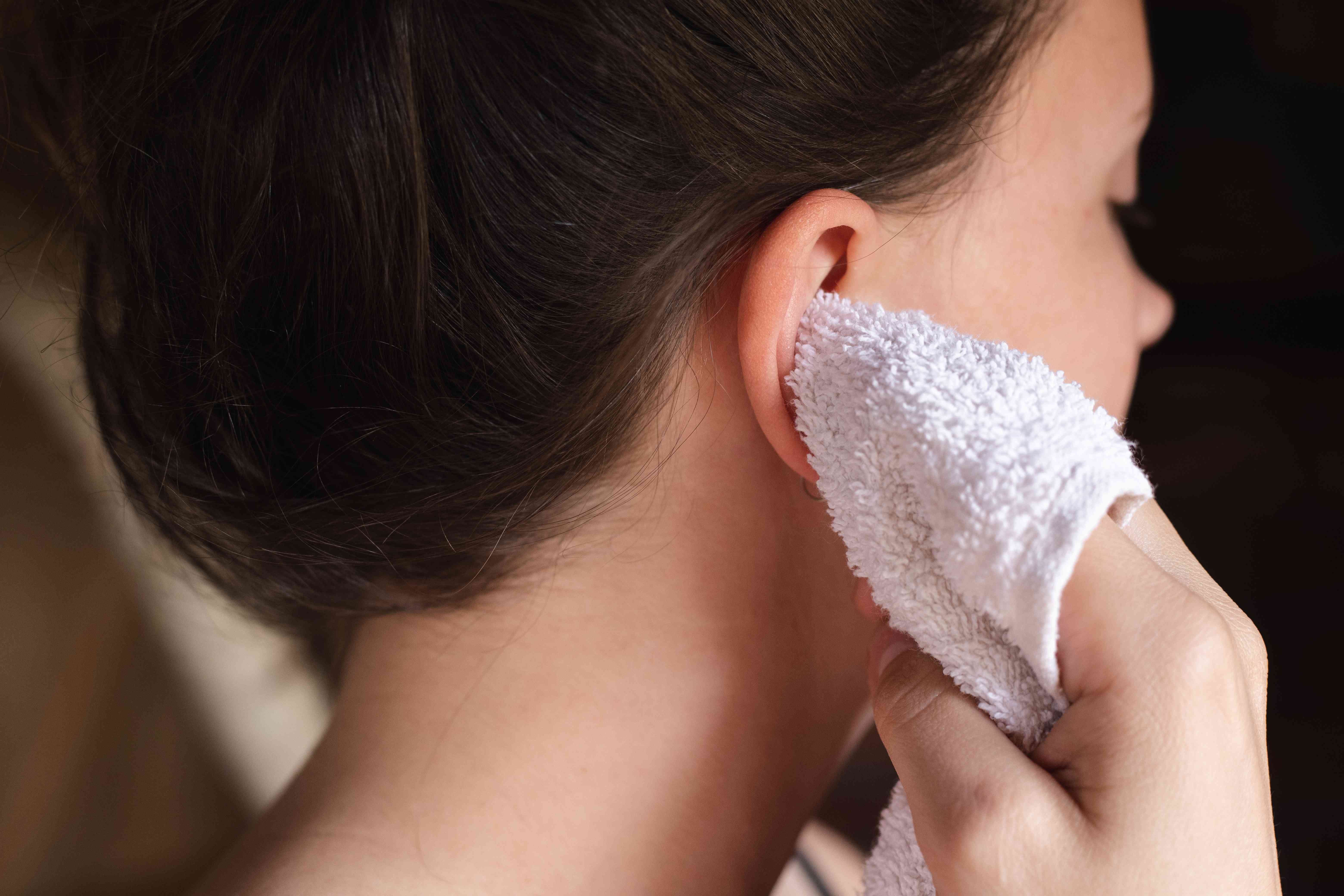 woman uses white washcloth wrapped around finger to gently dry ears