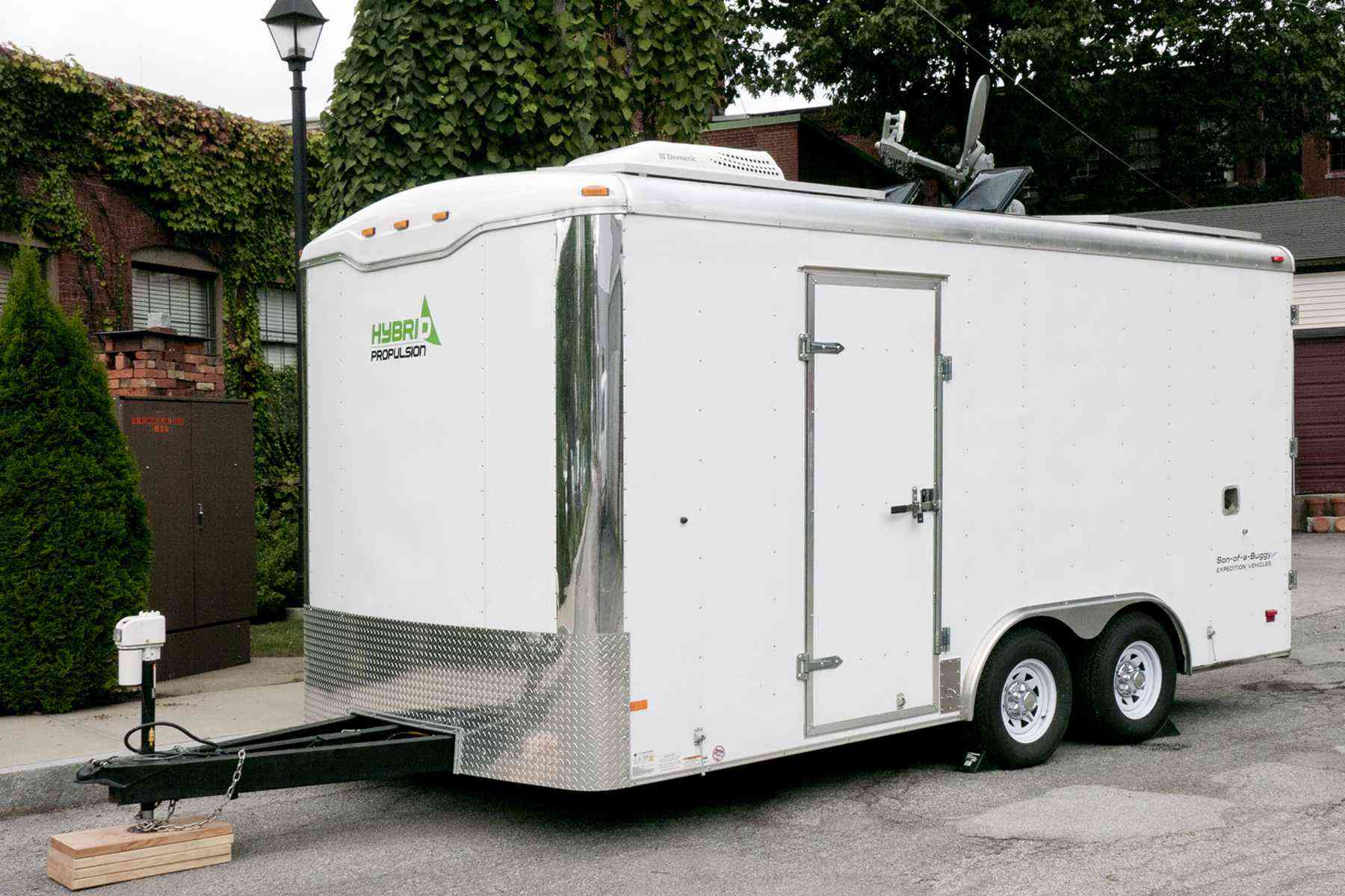A white trailer in front of a building