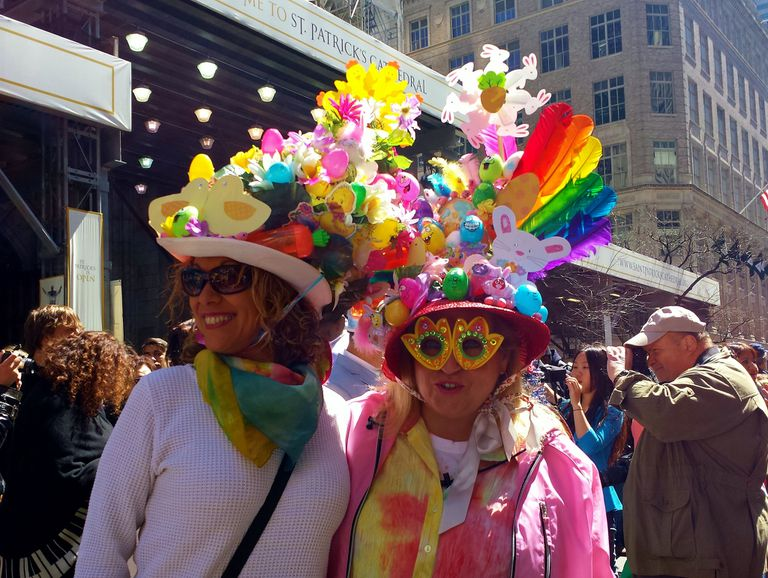 Two women with colorful Easter hats decorated with eggs and flowers