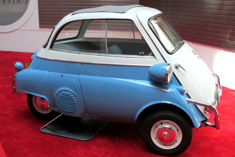 A blue 1957 BMW Isetta 2 in a showroom.