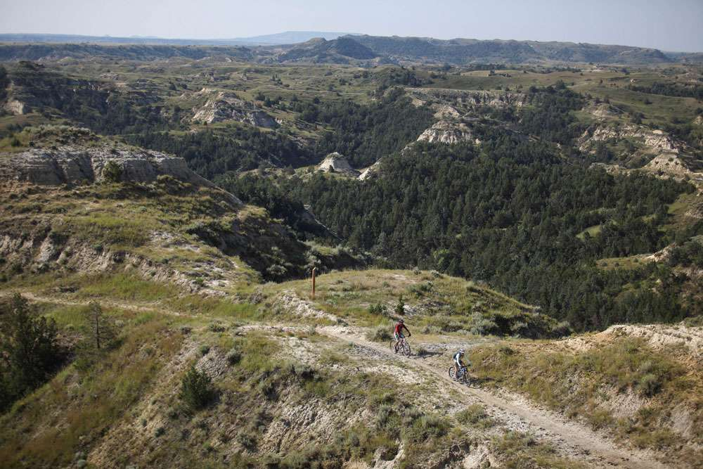 Two bike riders navigate a trail through forested bluffs