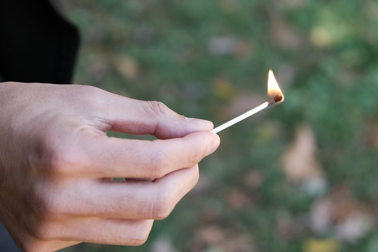 hero shot lit match with hand