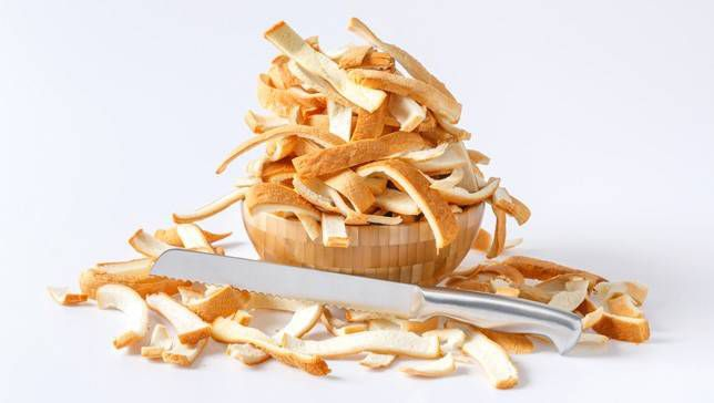 Bread crusts cut and piled into a bowl next to a bread knife