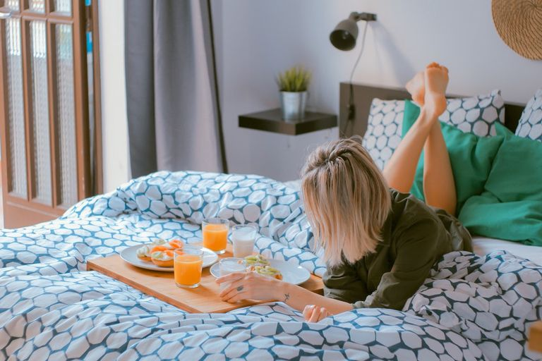 Young blonde woman having breakfast in bed