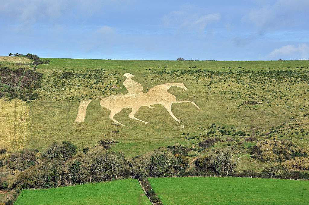Aerial view of Osmington White Horse and rider carved in a green hill under a blue sky on a sunny day above bright green lawn in the foreground
