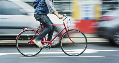 Man cycling on red bicycle in street with movement