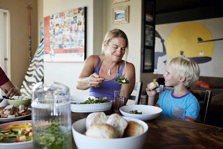 Mother serves vegetables to child