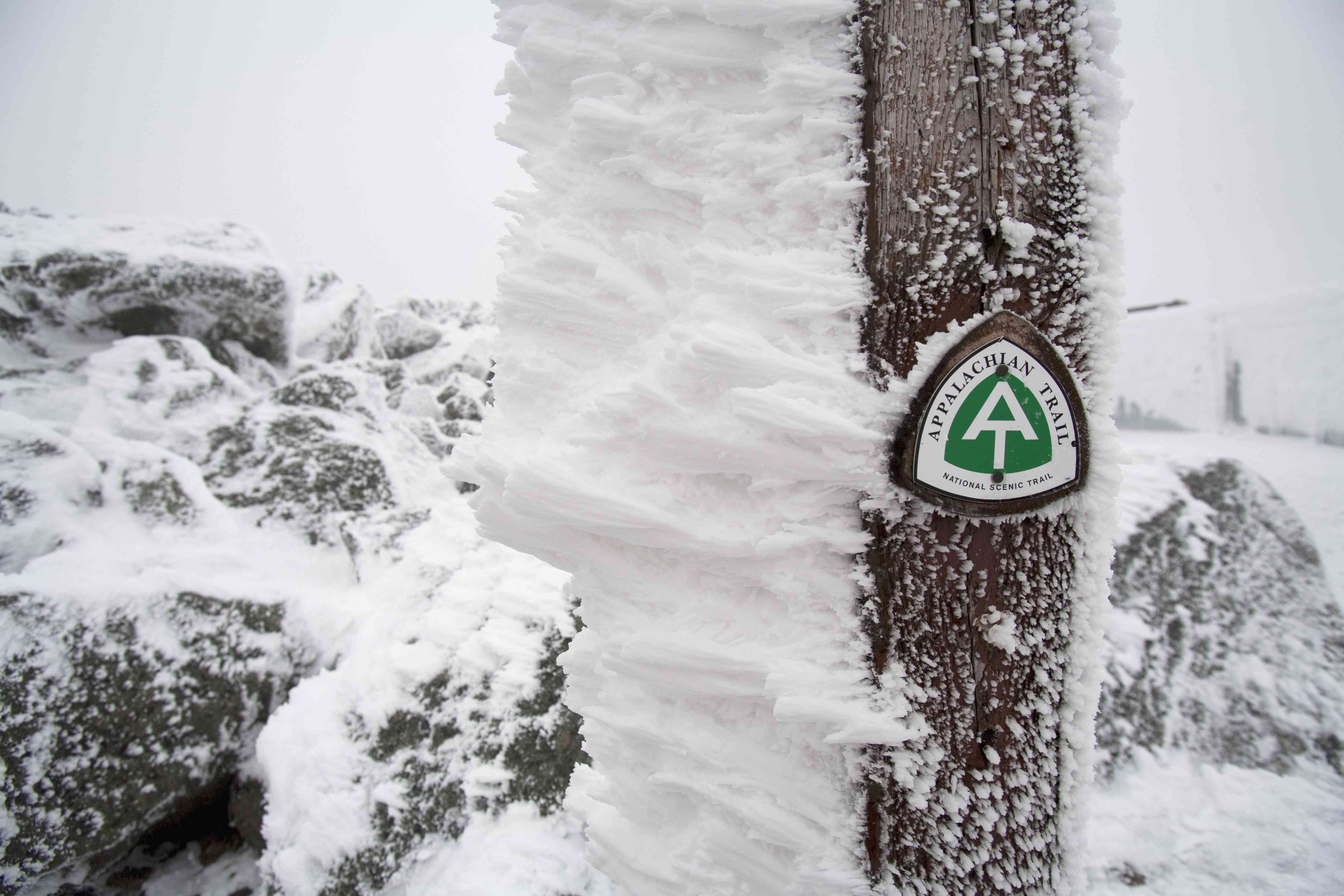A small, green snow covered sign points to the Appalachian Trail in the White Mountains of New Hampshire