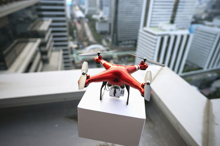A drone delivers a package on a skyscraper balcony.