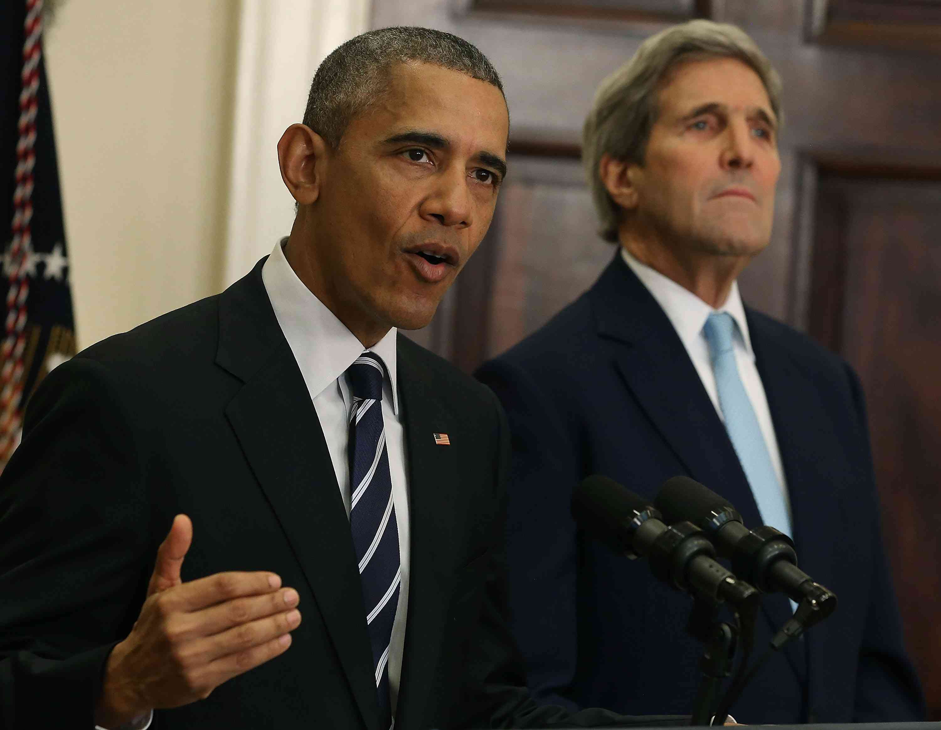 President Obama giving a speech with Secretary of State John Kerry in the background.
