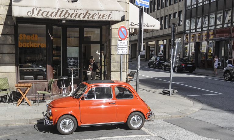 A red Fiat parked in an urban German street.