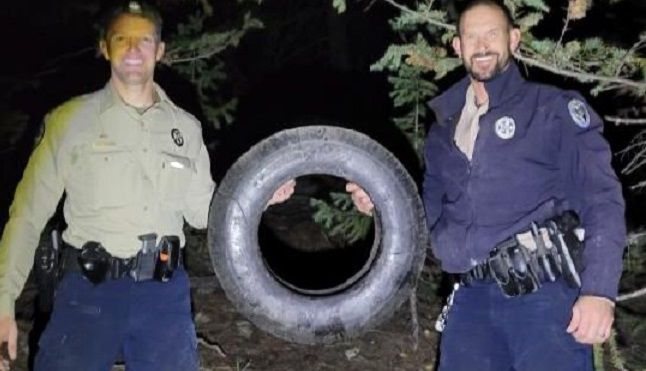 Wildlife officers Scott Murdoch (left) and Dawson Swanson (right) hold up the tire that was on the elk