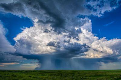 A thunderstorm microburst sits on a flat horizon.