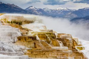 Travertine pools against mountains at Mammoth Hot Springs