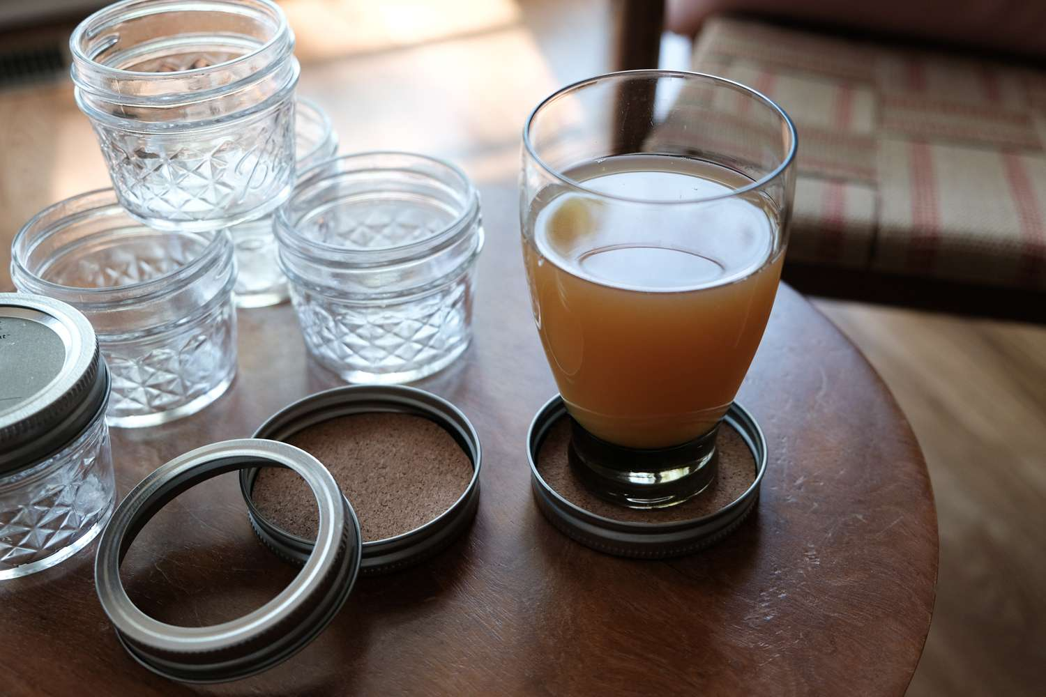 glass of warm beverage rests on DIY cork coaster made out of canning lid