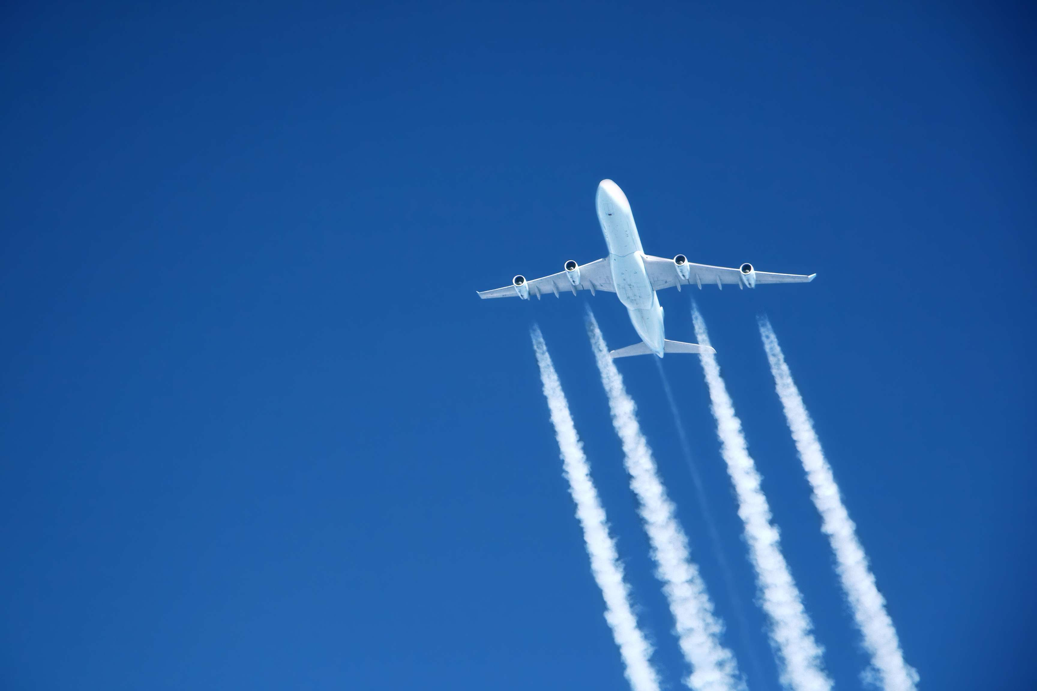 Airplane creating contrail clouds in blue sky