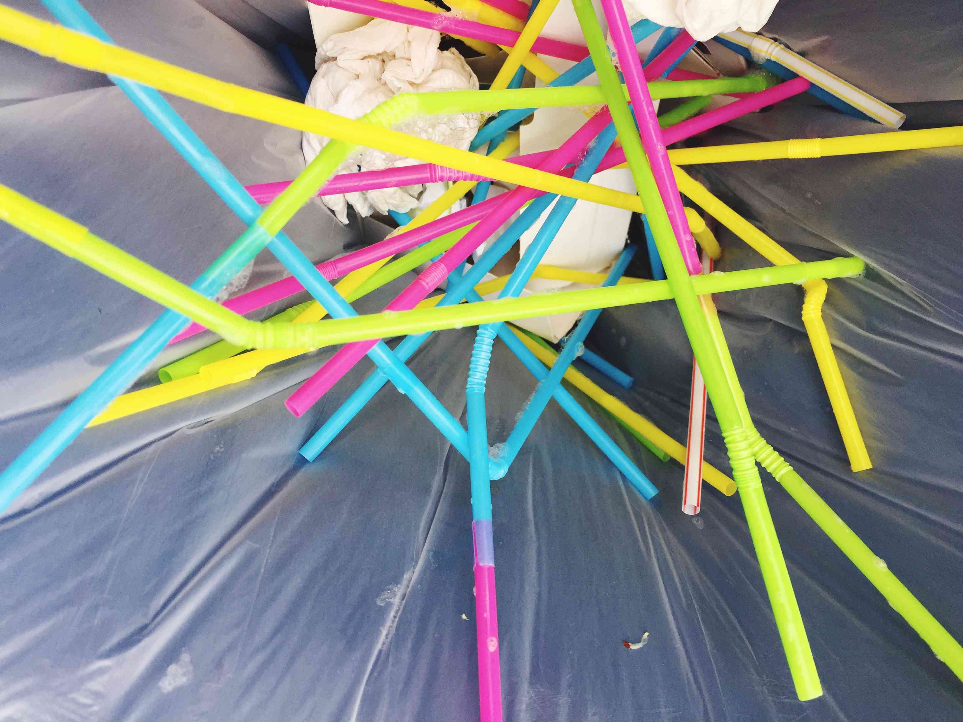 Close-Up Of Colorful Drinking Straws In Garbage Bin