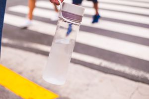 Closeup of a clear reusable water bottle, with a crosswalk in the background