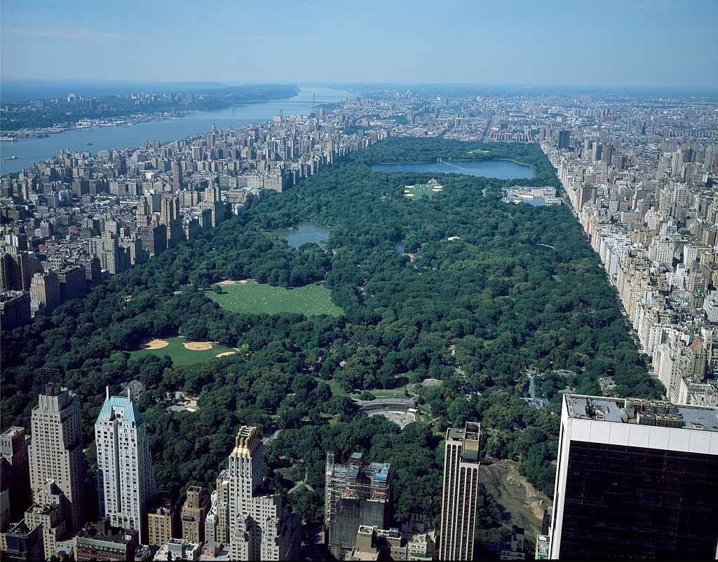 Aerial view of Central Park in New York City with green park surrounded by buildings and views of the river in the distance