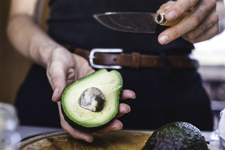 Woman holding half an avocado, ready to pop out the pit