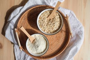 two bowls of oatmeal and colloidal oatmeal in woven basket on white waffle towel