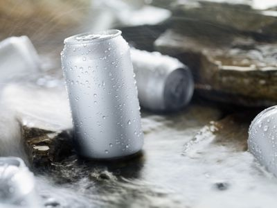 Silver cans with condensation drops, sitting in a stream of water