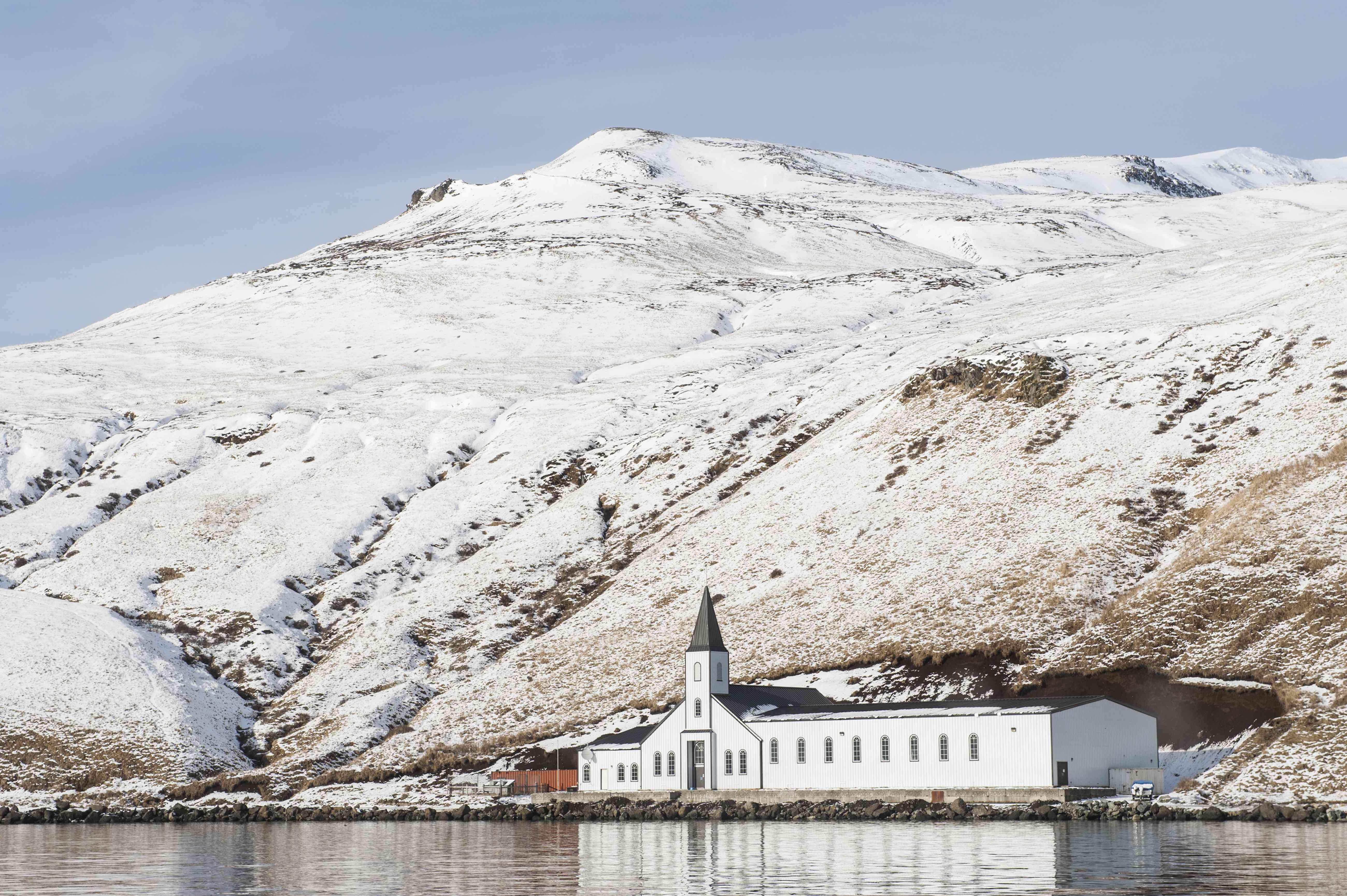 Church in front of snowy mountain in Akutan village