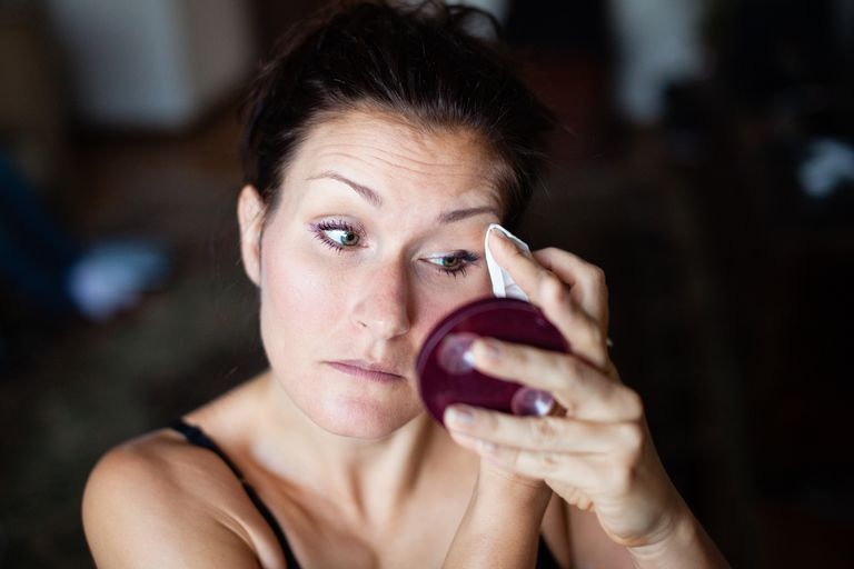 A woman wipes make up from her face with a make up cloth remover.