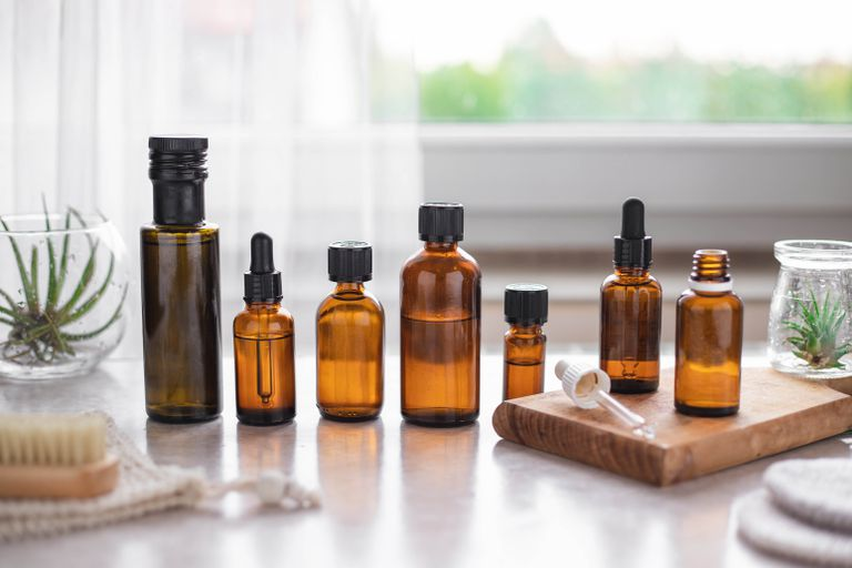 an array of amber-colored bottles filled with oil for a beauty cleansing method