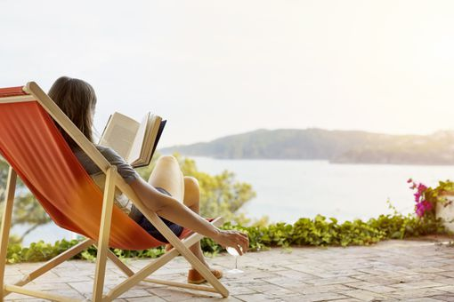 Woman reading book while relaxing on deck chair