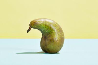 Misshapen pear sitting on a table