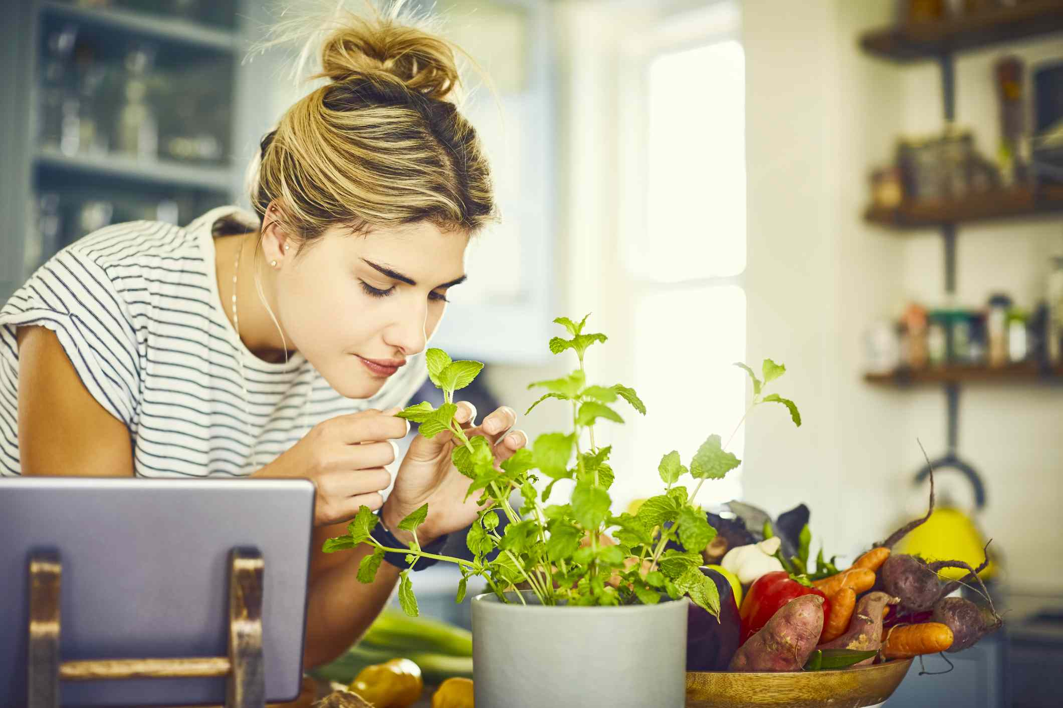 Woman in striped shirt smelling potted mint plant
