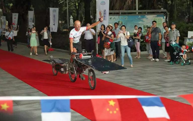 Man on a solar powered bike about to cross a finish line