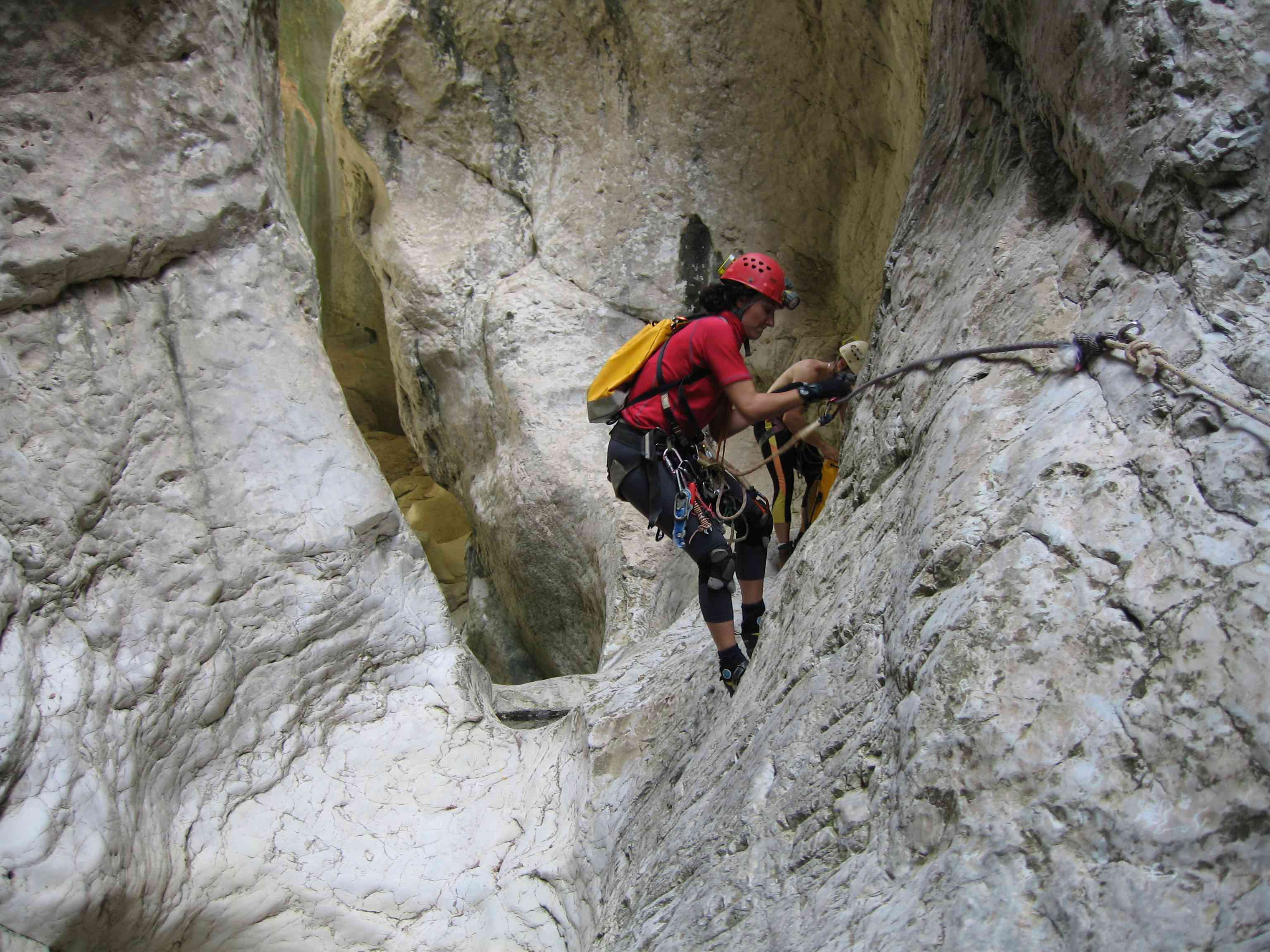 A couple secures their ropes while canyoning